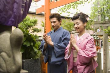 神社でお参りをする和服姿の男女