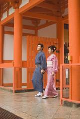 神社の門をくぐる和服姿の男女