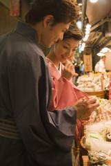 店先に並んだ魚を眺める和服姿の男女
