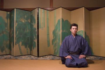 屏風の前に座る和服姿の男性
