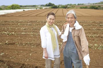 畑の中に立つシニアカップル