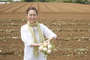 カブを持って畑の中に立つシニア女性