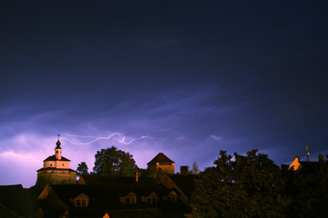 Storm lightning above old city with castle and a chapel