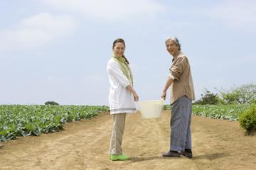 野菜かごを持つシニアカップル