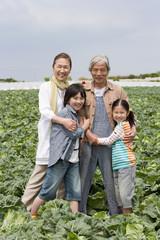 畑の中に立つ祖父母と孫2人