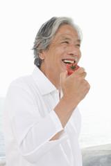 トマトを食べるシニア男性