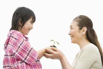 植物の苗を持つ男の子と祖母