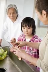 キッチンで調理する祖父母と孫