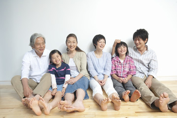 壁を背に座る3世代家族