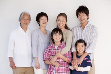 壁の前に立つ3世代家族