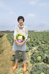 野菜かごを持って畑の前に立つ女性