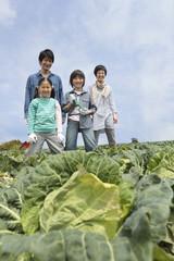 キャベツ畑の前に立つ親子4人