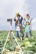 畑の中で記念撮影する親子4人