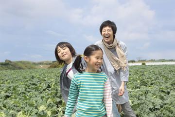 畑の中に立つ母と子供2人