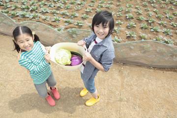 野菜かごを持って畑の前に立つ男の子と女の子