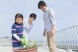 プランターの植物に水を遣る親子3人