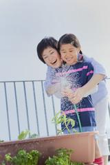ベランダで植物に水を遣る母と娘