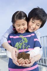 植物の苗を持って立つ母と娘