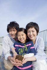植物の苗を持って立つ親子3人