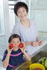 トマトを持って台所に立つ母と娘