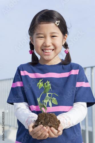 植物の苗を持って立つ女の子