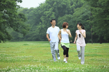 ウォーキングをする中年男女と若い女性