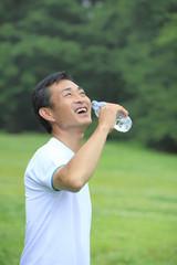ペットボトルの水を飲む中年男性
