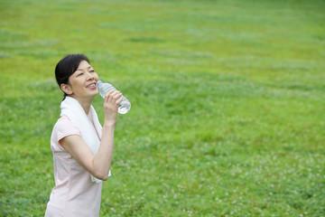 ペットボトルの水を飲む中年女性