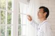 窓から外を見る中年男性