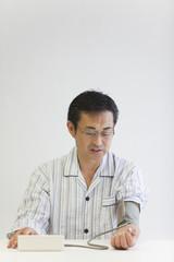 血圧を測る中年男性