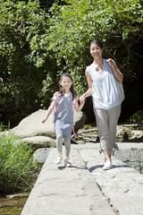 渓流の橋を渡る母親と娘
