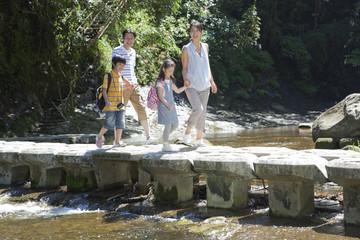 渓流の橋を渡る家族4人