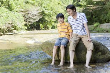 渓流の岩に腰掛ける父親と息子