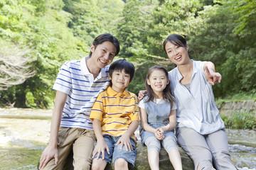渓流の岩に腰掛ける親子4人