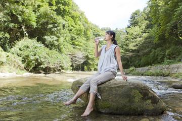 渓流の岩に腰掛けて水を飲む女性