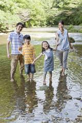 渓流で水遊びをする親子4人