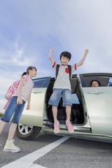 車から降りる男の子と女の子