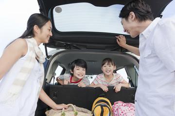 車のトランクを開ける家族4人