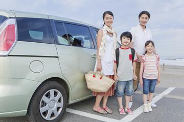 車の前に立つ家族4人
