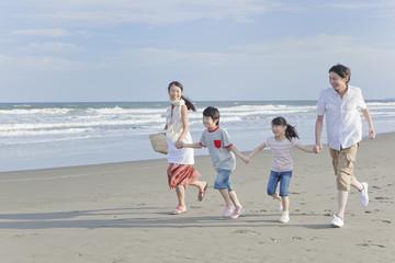 砂浜を手を繋いで走る家族4人