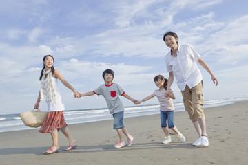 砂浜を手を繋いで歩く家族4人