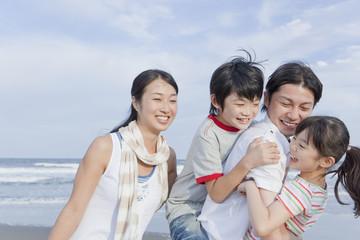 海岸で遊ぶ家族4人