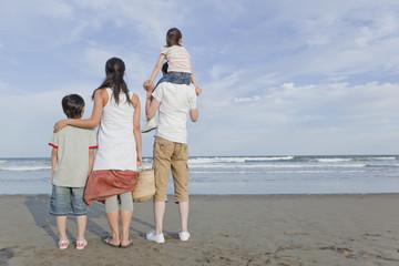 砂浜に立つ家族4人の後姿