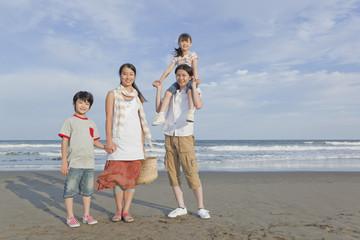 砂浜に立つ家族4人
