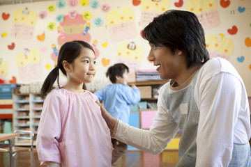 女の子に話しかける幼稚園教諭
