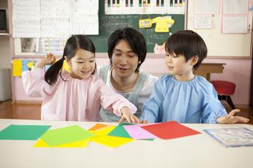 折り紙をする子供2人と幼稚園教諭