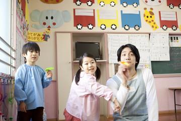 紙飛行機を飛ばす子供2人と幼稚園教諭