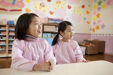 幼稚園の教室で座っている女の子2人