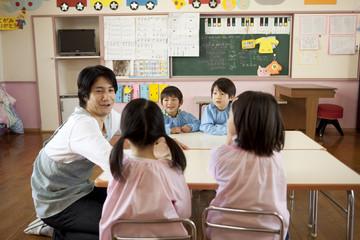 教室で話をする幼稚園児と幼稚園教諭