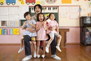 子供3人を抱く幼稚園教諭